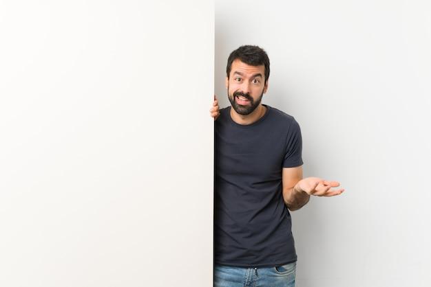 Jovem bonito com barba segurando um cartaz grande e vazio, fazendo o gesto de dúvidas
