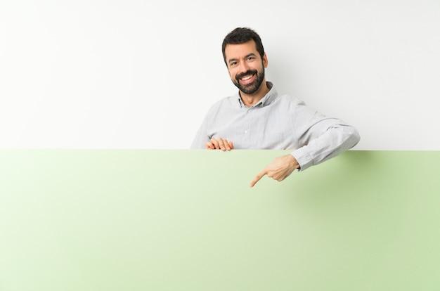 Jovem bonito com barba segurando um cartaz vazio verde grande e apontando-o