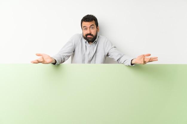 Jovem bonito com barba segurando um cartaz vazio verde grande infeliz por não entender algo