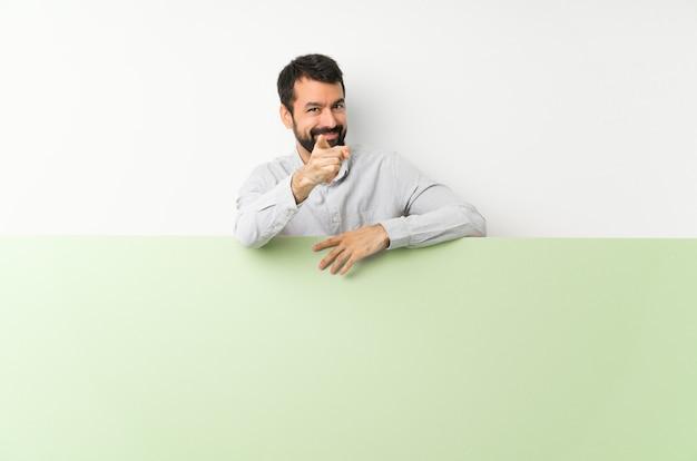 Jovem bonito com barba, segurando um cartaz verde grande vazio aponta o dedo para você com uma expressão confiante