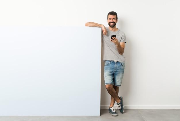 Jovem bonito com barba segurando um grande cartaz azul vazio, enviando uma mensagem com o celular