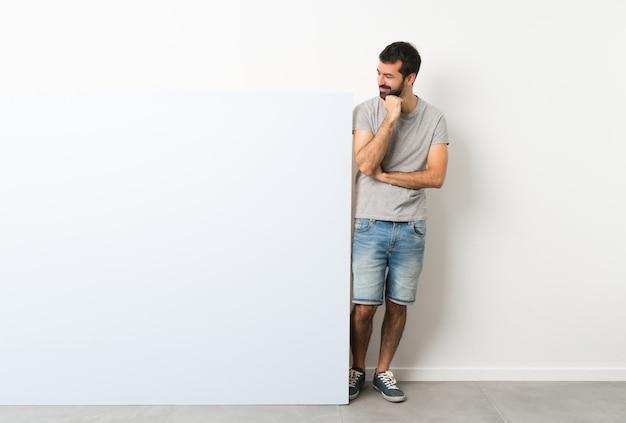 Jovem bonito com barba segurando um grande cartaz azul vazio, olhando para o lado