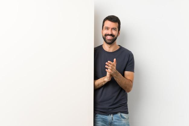 Jovem bonito com barba segurando um grande cartaz vazio aplaudindo após apresentação em uma conferência