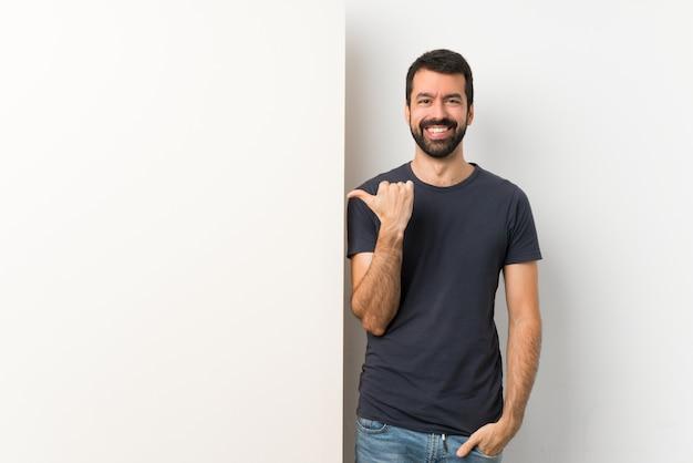 Jovem bonito com barba segurando um grande cartaz vazio, apontando para o lado para apresentar um produto