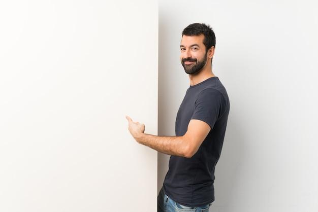 Jovem bonito com barba segurando um grande cartaz vazio apontando para trás
