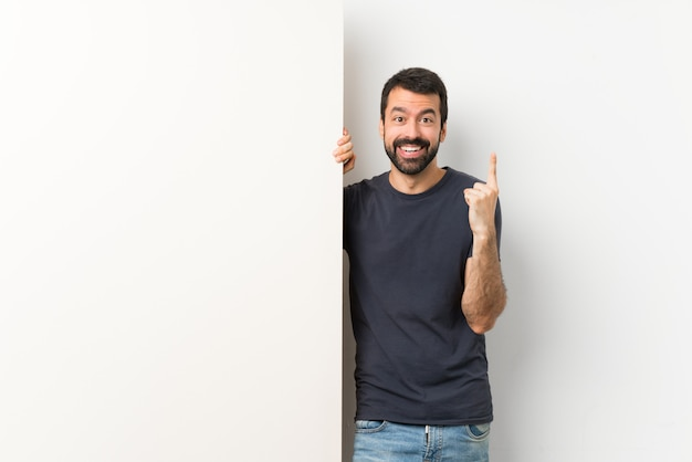 Jovem bonito com barba segurando um grande cartaz vazio apontando uma ótima idéia