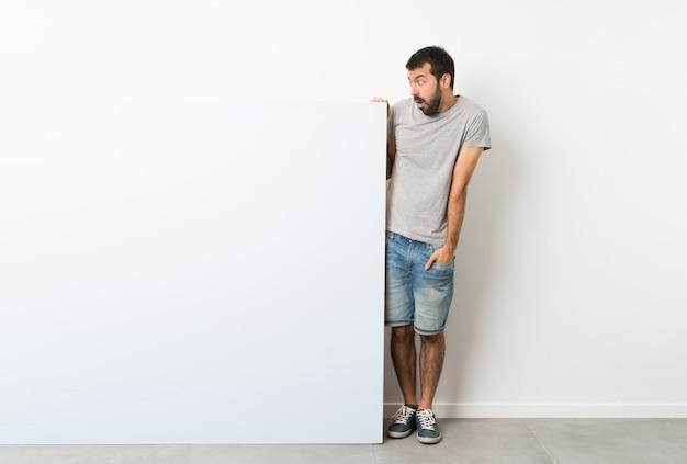 Jovem bonito com barba segurando um grande cartaz vazio azul com expressão facial de surpresa