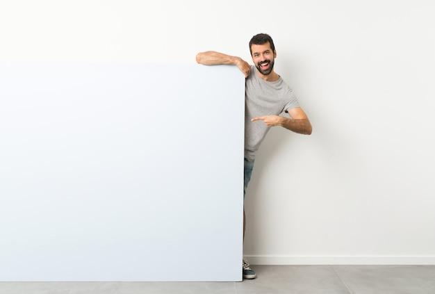 Jovem bonito com barba segurando um grande cartaz vazio azul e apontando-o