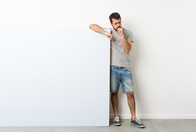 Jovem bonito com barba segurando um grande cartaz vazio azul está sofrendo com tosse e se sentindo mal