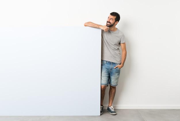 Jovem bonito com barba segurando um grande cartaz vazio azul pensando uma idéia enquanto olha para cima