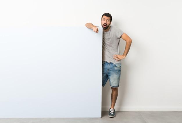 Jovem bonito com barba segurando um grande cartaz vazio azul surpreso e apontando a frente
