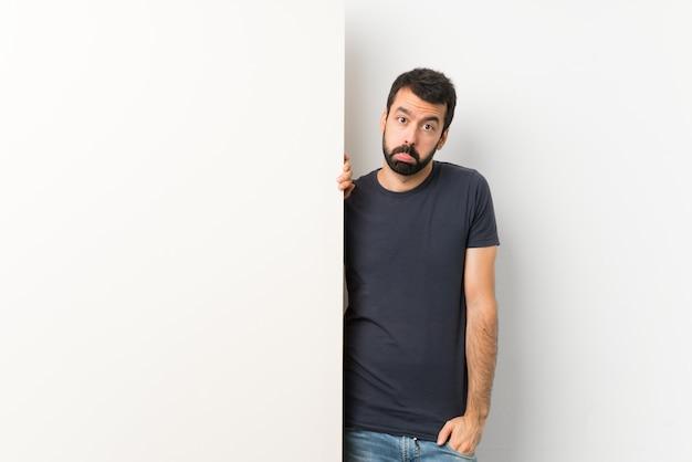Jovem bonito com barba segurando um grande cartaz vazio com expressão triste e deprimida