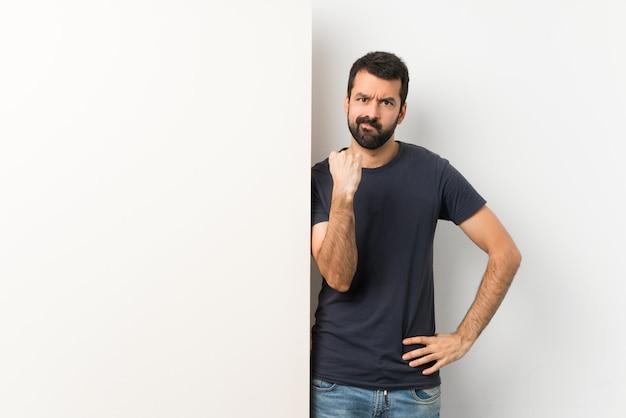 Jovem bonito com barba segurando um grande cartaz vazio com gesto de raiva