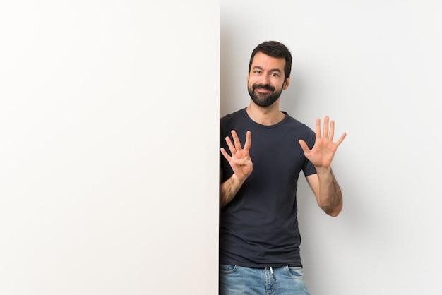 Jovem bonito com barba segurando um grande cartaz vazio contando nove com os dedos