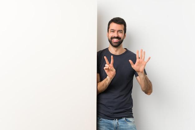 Jovem bonito com barba segurando um grande cartaz vazio, contando sete com os dedos