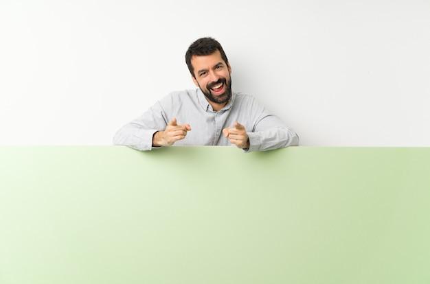 Jovem bonito com barba, segurando um grande cartaz vazio verde aponta o dedo para você enquanto sorrindo