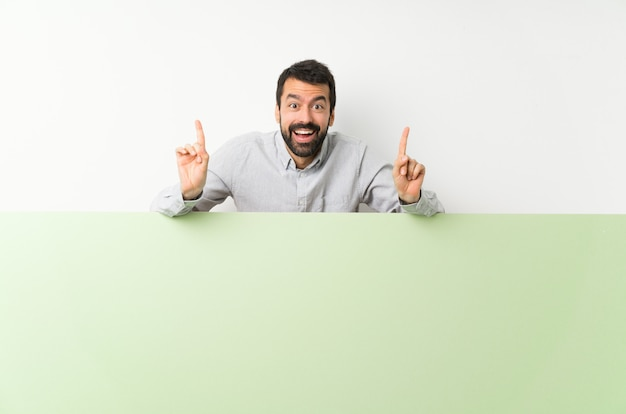 Jovem bonito com barba segurando um grande cartaz vazio verde apontando para cima uma ótima idéia