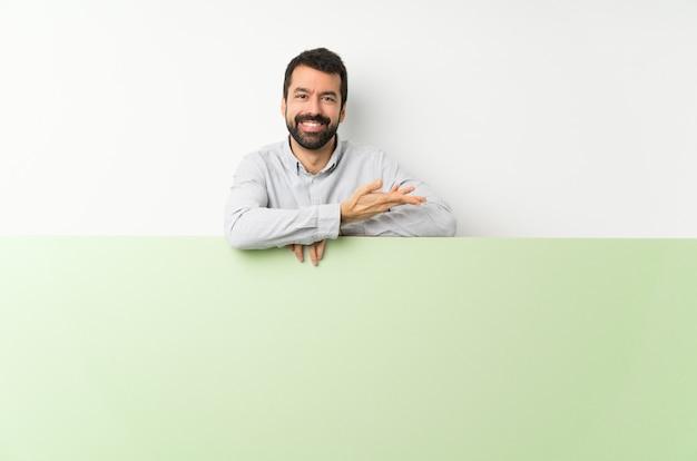 Jovem bonito com barba segurando um grande cartaz vazio verde, apresentando uma idéia enquanto olha sorrindo para