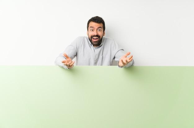 Jovem bonito com barba segurando um grande cartaz vazio verde com expressão facial chocado