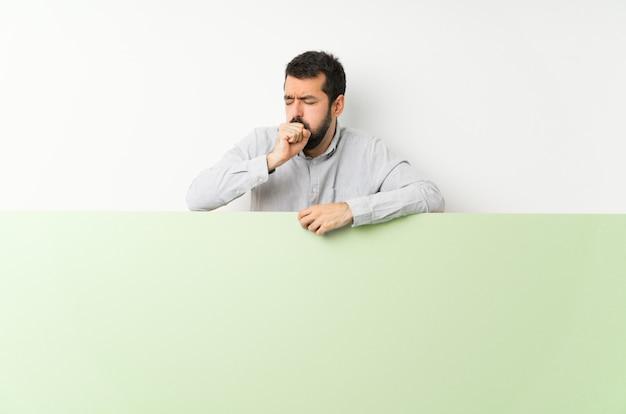 Jovem bonito com barba, segurando um grande cartaz vazio verde está sofrendo com tosse e se sentindo mal