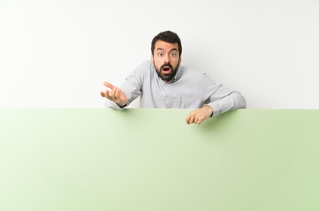 Jovem bonito com barba segurando um grande cartaz vazio verde, fazendo o gesto de dúvidas
