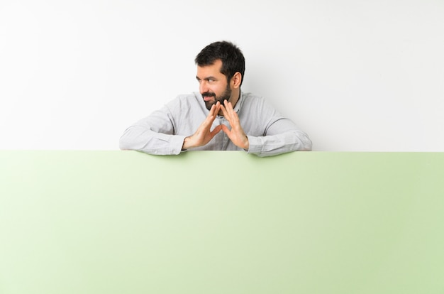 Jovem bonito com barba segurando um grande cartaz vazio verde planejando algo