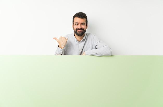 Jovem bonito com barba segurando um grande cartaz vazio verde