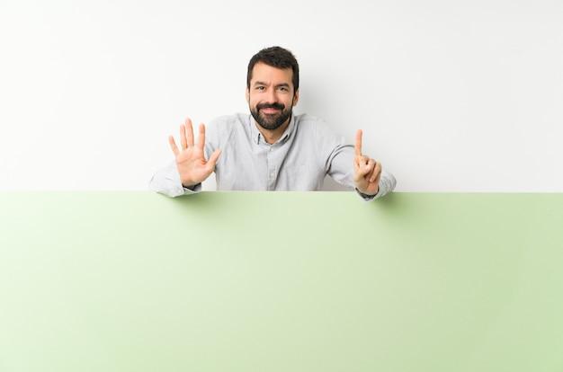 Jovem bonito com barba segurando um grande cartaz verde vazio, contando seis com os dedos