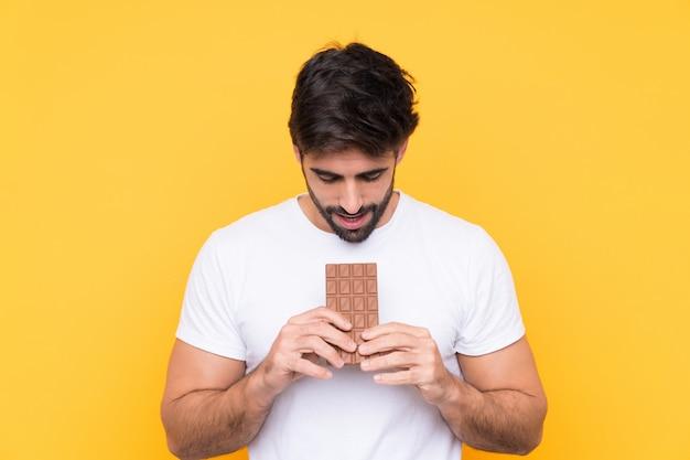 Jovem bonito com barba sobre parede amarela isolada, comendo uma tablete de chocolate