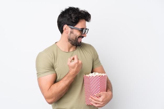 Jovem bonito com barba sobre parede branca isolada com óculos 3d e segurando um grande balde de pipocas enquanto olha de lado