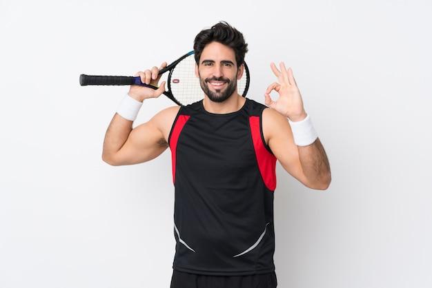 Jovem bonito com barba sobre parede branca isolada, jogando tênis e fazendo sinal de ok
