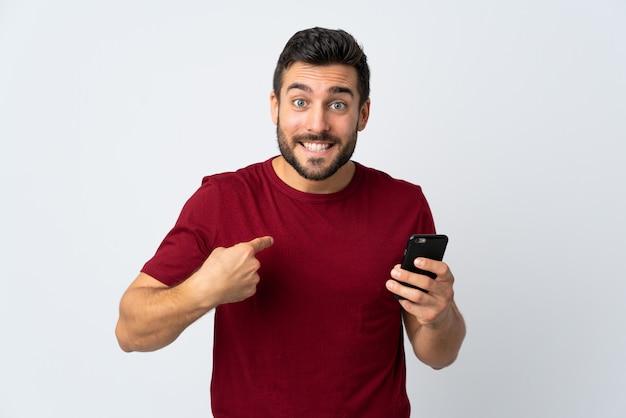Jovem bonito com barba usando telefone celular isolado no branco com expressão facial de surpresa