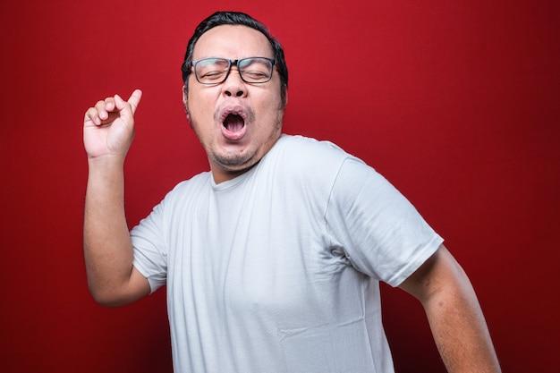 Jovem bonito com barba vestindo camiseta branca e óculos sobre fundo vermelho dançando feliz e alegre, sorrindo, movendo-se casual e confiante ouvindo música Foto Premium