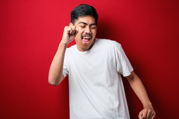Jovem bonito com barba vestindo camiseta branca sobre fundo vermelho dançando feliz e alegre, sorrindo, movendo-se casual e confiante ouvindo música