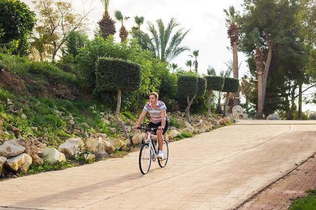 Jovem bonito com bicicleta e capacete no parque em dia ensolarado.