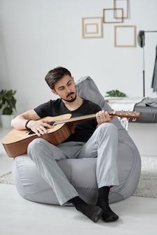 Jovem bonito com bigode preto sentado em um saco de feijão e tocando violão em casa durante a quarentena