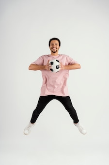 Jovem bonito com bola de futebol pulando