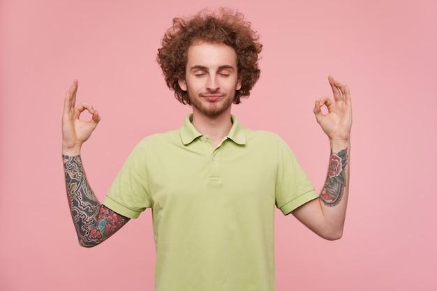 Jovem bonito com cabelo castanho cacheado tatuado, mantendo os olhos fechados enquanto medita e cruzando os dedos em gesto de mudra, isolado sobre um fundo rosa
