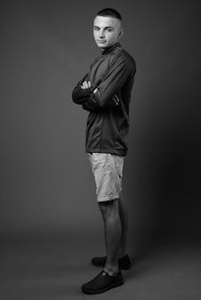 Jovem bonito com cabelo curto, vestindo uma camisa de gola alta contra a parede cinza. preto e branco