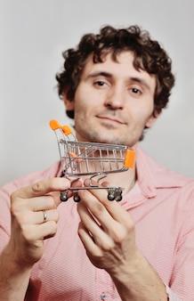 Jovem bonito com cabelo encaracolado com um carrinho de supermercado pequeno sobre um fundo claro