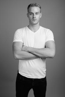 Jovem bonito com cabelo loiro contra uma parede cinza em preto e branco