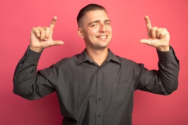 Jovem bonito com camisa cinza sorrindo alegremente mostrando o gesto do tamanho com os dedos medindo o símbolo em pé sobre a parede rosa