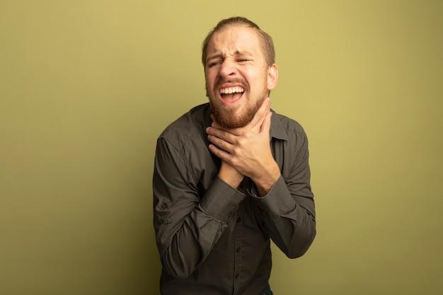 Jovem bonito com camisa cinza sufocando de mãos dadas em pânico na garganta