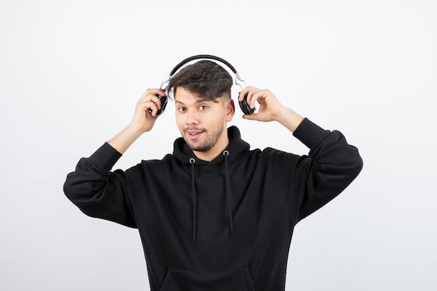 Jovem bonito com capuz preto usando grandes fones de ouvido de música sem fio