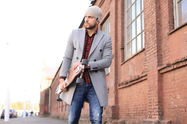 Jovem bonito com casaco cinza e chapéu andando na rua, usando longboard.