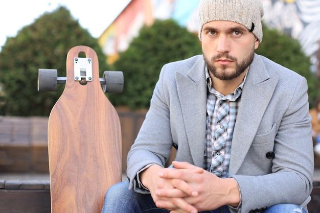 Jovem bonito com casaco cinza e chapéu, descansando, sentado com longboard. conceito de skate urbano.