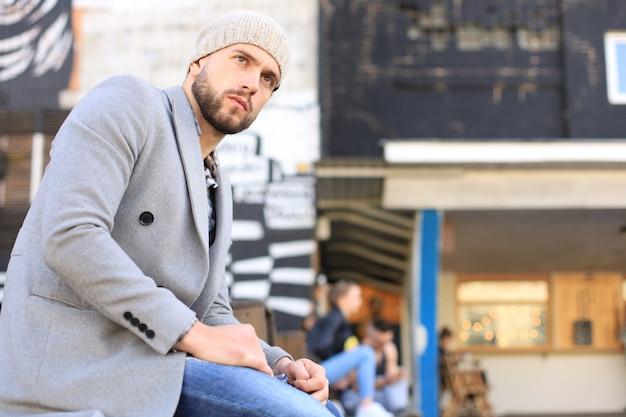 Jovem bonito com casaco cinza e chapéu, descansando, sentado em um banco. conceito urbano.