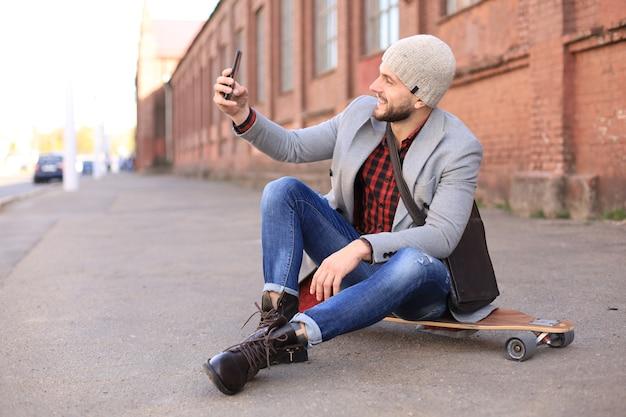 Jovem bonito com casaco cinza e chapéu sentado no longboard e tomando selfie na rua da cidade.