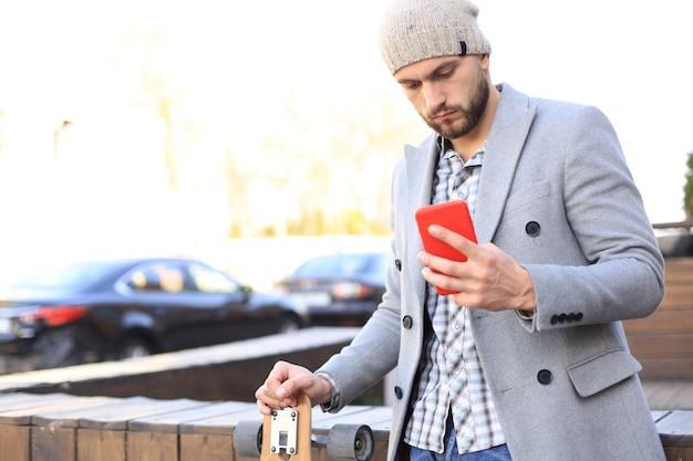 Jovem bonito com casaco cinza e chapéu usando smartphone, descansando, em pé com longboard. conceito de skate urbano.