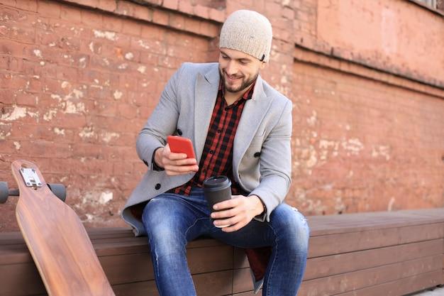 Jovem bonito com casaco cinza e chapéu usando smartphone, descansando, sentado com longboard. conceito de skate urbano.